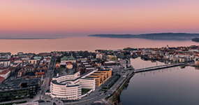 Drone photo of campus with Jönköping and lake Vättern in the background during sun set